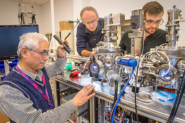 Brookhaven Lab physicists (from left to right) Genda Gu, Tonica Valla, and Ilya Drozdov at OASIS, a new on-site experimental machine for growing and characterizing oxide thin films, such as those of a class of high-temperature superconductors (HTS) known as the cuprates